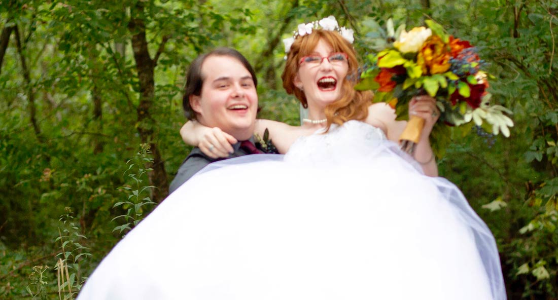 Robin Hall lifts Sarah Caitlin Hall, wearing a gown she purchased from Goodwill, after their wedding in west Nashville. Photo by Taylor J Photography