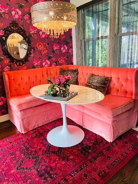 "This coral velvet, tufted banquette Stephanie Bowman bought for $50 from Goodwill in Nashville is now the centerpiece of her kitchen nook. ""It (banquette) looks like it is something that has a story behind it, which is one of the things we love about bringing second-hand pieces into our house,"" she says."